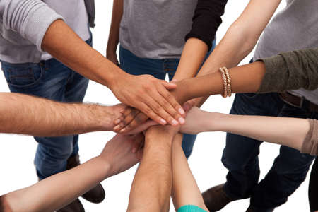 Photo pour High angle view of multiethnic college students stacking hands against white background - image libre de droit