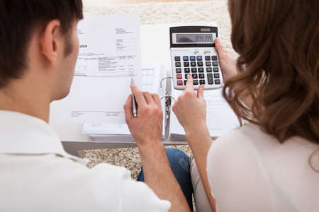Photo for Portrait of young happy couple calculating budget - Royalty Free Image
