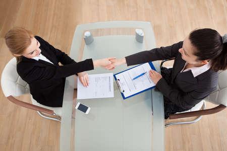 Photo pour Portrait Of Two Happy Businesswoman Having Handshake In Office - image libre de droit