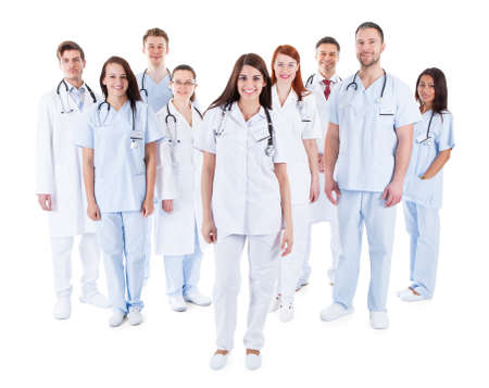 Foto de Large diverse group of medical staff in white uniforms standing grouped behind a handsome middle-aged bearded doctor or physician isolated on white - Imagen libre de derechos