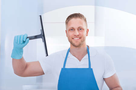 Photo pour Male janitor using a squeegee to clean a window in an office wearing an apron and gloves as he works - image libre de droit