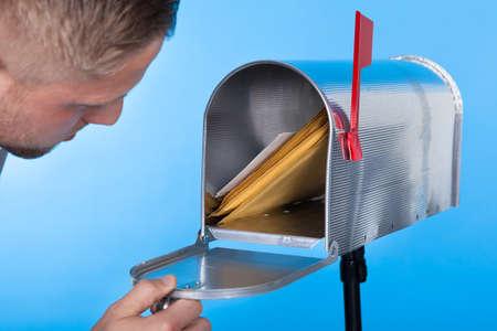 Foto de Man opening his mailbox to remove mail inside  close up of his hand on the open door against a blue sky - Imagen libre de derechos