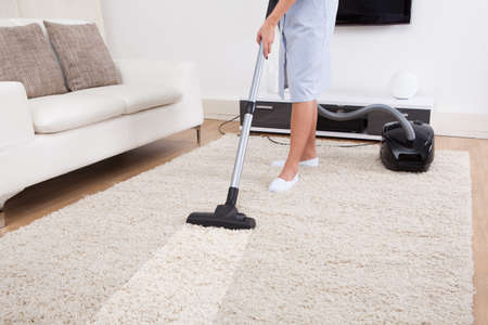 Photo pour Cropped image of young maid cleaning carpet with vacuum cleaner at home - image libre de droit