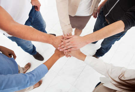 Photo pour Cropped image of businesspeople stacking hands in office - image libre de droit