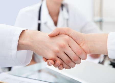 Photo pour Cropped image of doctors shaking hands at desk in clinic - image libre de droit