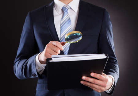 Photo for Midsection of businessman examining documents with magnifying glass against black background - Royalty Free Image
