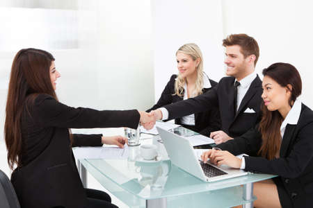 Photo for Business colleagues shaking hands at desk in office - Royalty Free Image