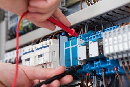 Foto de Closeup of male electrician examining fusebox with multimeter probe - Imagen libre de derechos