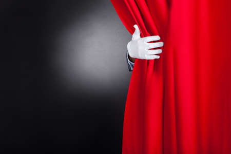 Photo for Cropped image of magician opening red stage curtain - Royalty Free Image