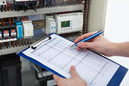 Foto de Cropped image of male electrician holding clipboard while examining fusebox - Imagen libre de derechos