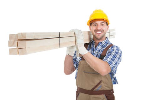 Foto de Full length portrait of young manual worker carrying wooden planks over white background - Imagen libre de derechos