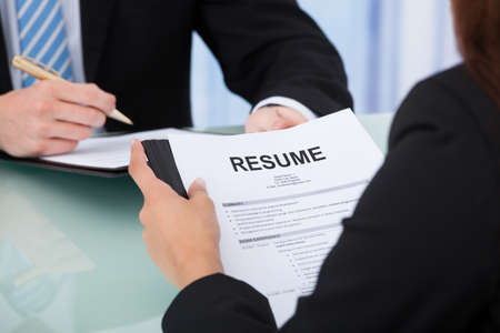 Photo for Cropped image of female candidate holding resume at desk during interview - Royalty Free Image