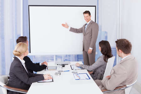 Foto de Young businessman giving presentation to colleagues in office - Imagen libre de derechos