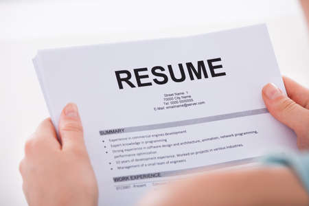 Photo for Cropped image of young woman holding resume over white  - Royalty Free Image