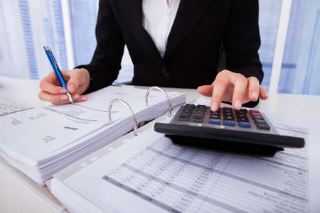 Photo pour Midsection of businesswoman calculating tax at office desk - image libre de droit