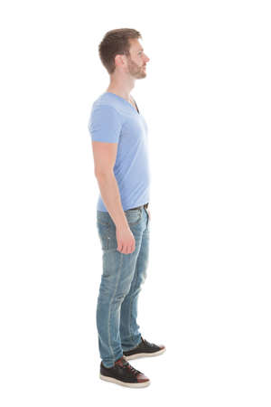 Photo for Full length side view of young man standing isolated on white  - Royalty Free Image