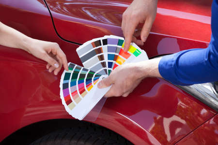 Photo pour Cropped image of mechanic showing color samples to customer against car - image libre de droit