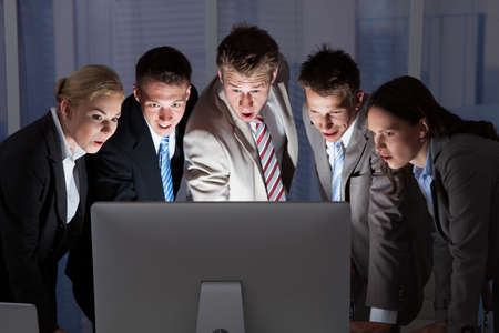Surprised young business people looking at computer monitor in office