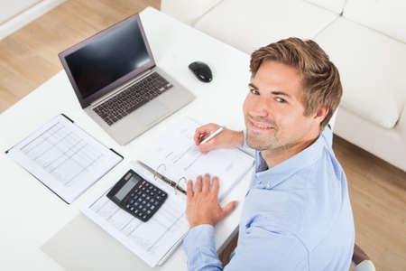 Photo pour High angle portrait of businessman calculating tax at desk in office - image libre de droit