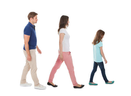 Foto de Full length side view of family walking in a row isolated over white background - Imagen libre de derechos