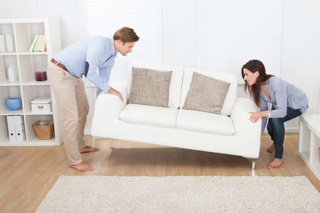 Photo for Full length of happy couple placing sofa in living room of new home - Royalty Free Image