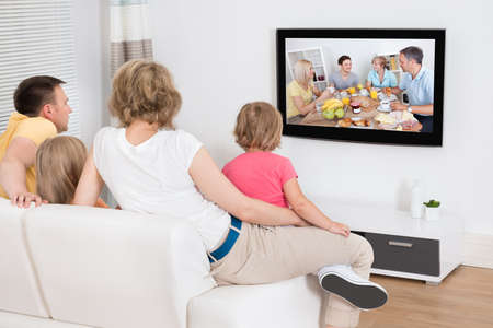 Foto de Young Family Watching TV Together At Home - Imagen libre de derechos