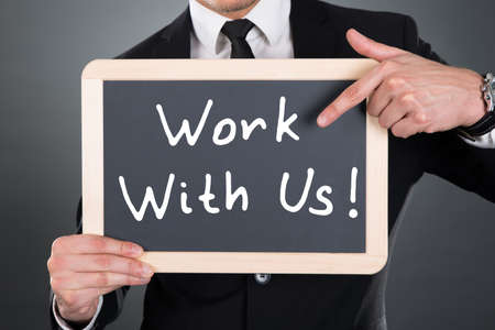 Photo pour Midsection of young businessman pointing Work With Us sign on slate over gray background - image libre de droit