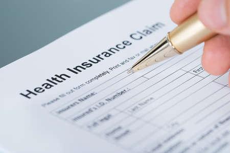 Photo pour Hand filling health insurance claim form. Closeup shot - image libre de droit