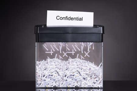 Foto de Shredded destroying confidential document over black background - Imagen libre de derechos