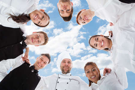 Photo pour Directly below portrait of happy chef and waiters standing in huddle against sky - image libre de droit