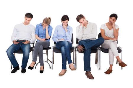 Foto de Full length of bored businesspeople sitting on chairs against white background - Imagen libre de derechos