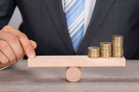 Photo pour Midsection of businessman balancing coins on wooden seesaw at table - image libre de droit