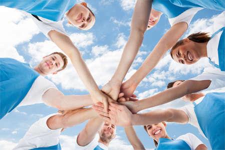 Photo pour Directly below shot of diverse professional cleaners piling hands against sky - image libre de droit