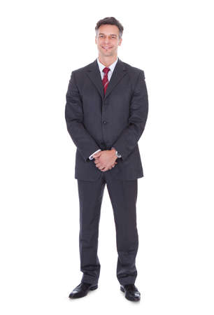 Photo for Full length portrait of smiling businessman with hands clasped standing against white background - Royalty Free Image