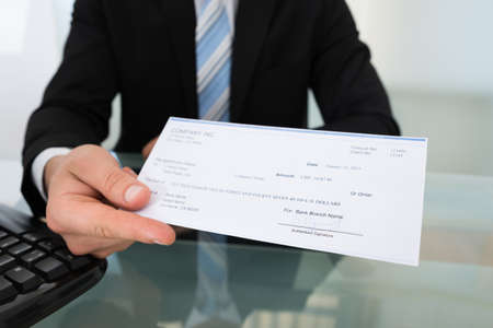 Photo pour Midsection of businessman giving cheque at desk in office - image libre de droit