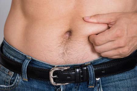 Photo pour Closeup midsection of man holding fat belly - image libre de droit