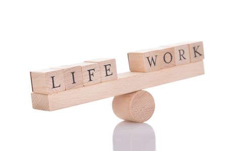 Foto de Wooden seesaw representing imbalance between Life and Work isolated over white background - Imagen libre de derechos