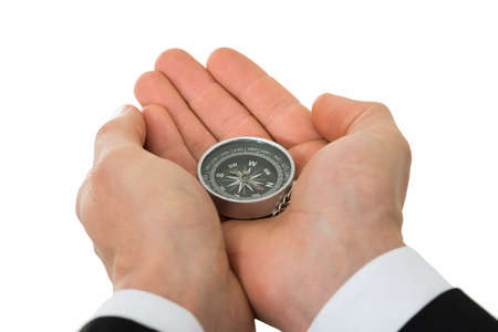 Closeup of businessman's hands holding compass over white background