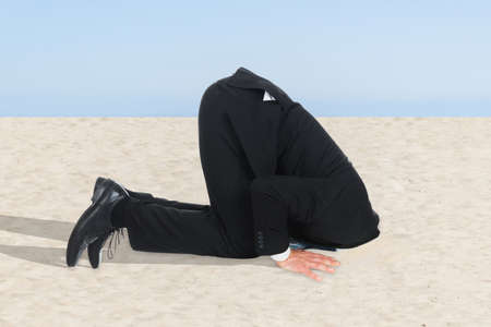 Foto de Side view of businessman hiding his head in sand - Imagen libre de derechos