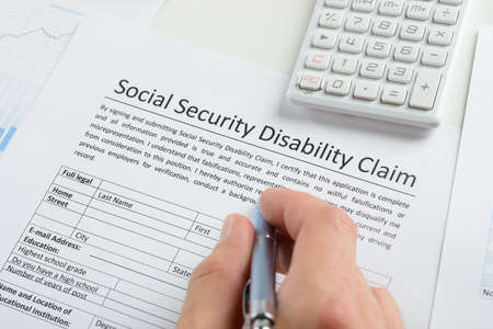 Photo pour Close-up Of Person Hand With Pen And Calculator Filling Social Security Disability Claim Form - image libre de droit