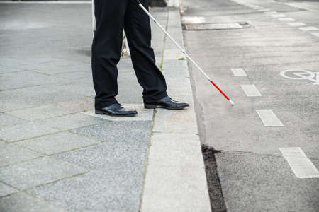 Photo pour Low Section Of A Blind Person Crossing Street - image libre de droit