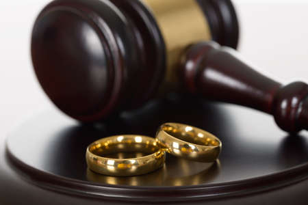 Photo pour Close-up Of Wedding Rings And Wooden Gavel - image libre de droit