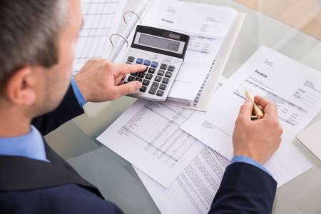 Photo pour Over The Shoulder View Of Businessman Calculating Invoices Using Calculator - image libre de droit