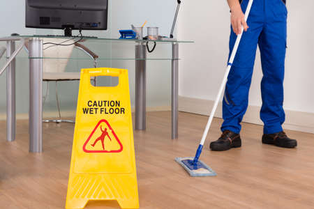 Photo pour Close-up Of Janitor Mopping With Wet Floor Sign In Office - image libre de droit