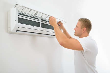 Foto de Portrait Of A Young Man Adjusting Air Conditioning System - Imagen libre de derechos
