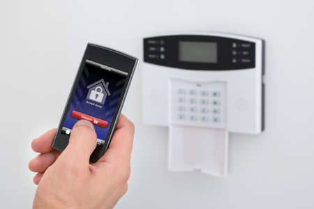 Foto de Security Alarm Keypad With Person Disarming The System With Remote Controller - Imagen libre de derechos