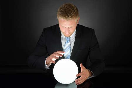 Photo pour Portrait Of Businessman Predicting Future With Crystal Ball - image libre de droit