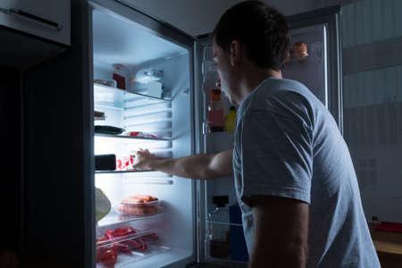 Foto de Portrait Of A Man Taking Food From Refrigerator - Imagen libre de derechos