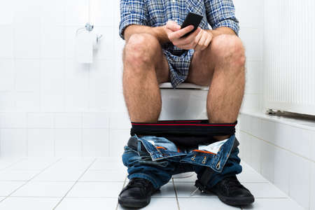 Close-up Of  A Man In Toilet Using Cellphone