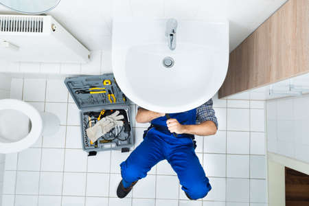 Photo pour High Angle View Of Male Plumber Repairing A Sink In Bathroom - image libre de droit